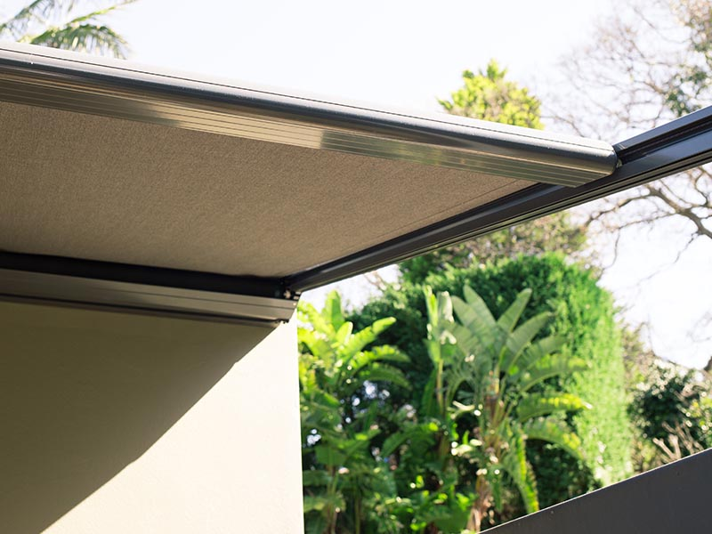 retractable patio awning over decks and balconies reduce the heat of the sun