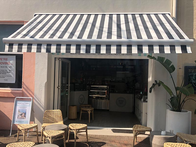 retractable folding arm awning with black and white striped fabric