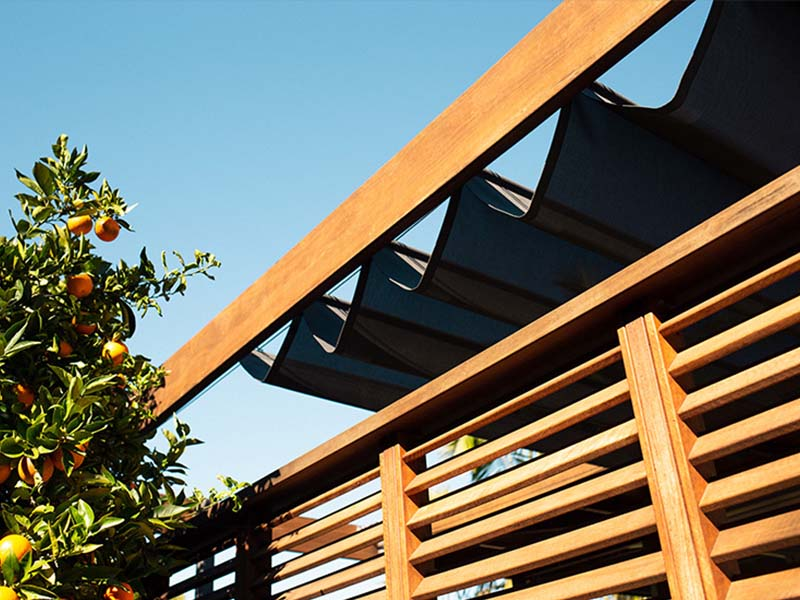 retractable shade sail extends and retracts along stainless steel cables protecting outdoor areas from UV rays and heat