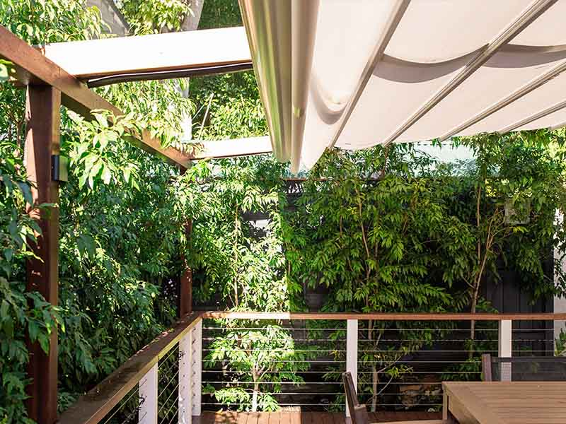 retractable awning over timber pergola frame gives sun, wind and rain protection
