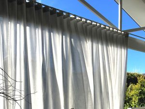 Outdoor curtains over deck for protection from the sun and privacy