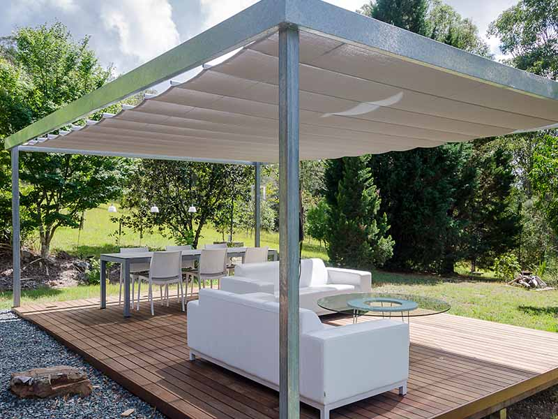 Free standing outdoor cabana with retractable shade sail