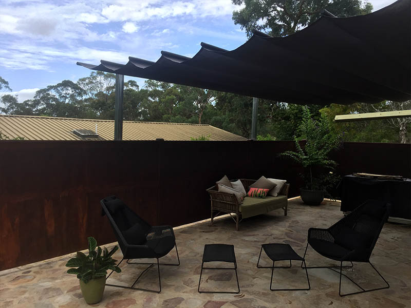 retractable shade sail over courtyard for outdoor living