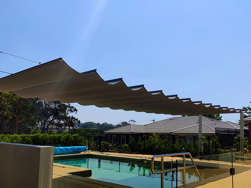 Retractable shade sail over pool