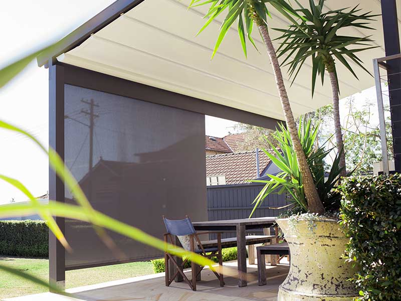 Retractable straight drop awning used as a screen in outdoor living area