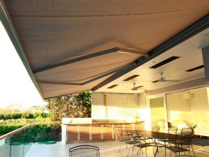 Extended folding arm awning with heaters over outdoor area