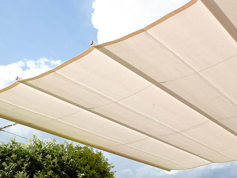 retractable shade sail over outdoor area for shade